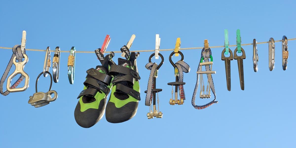Bild zeigt Kletterausrüstung zum Klettern mit Karabinern und Kletterschuhen.